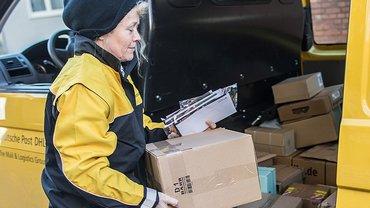 Zustellerin mit Paketen vor ihrem Auto, Deutsche Post AG